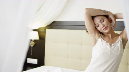 Joyful woman posing on bed in white sleepwear shirt