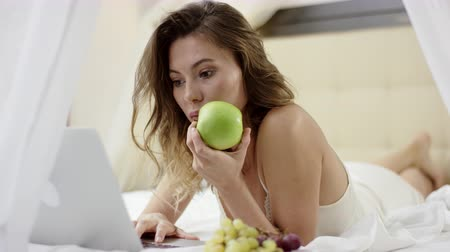 Young woman surfing the Internet on her laptop and holding apple