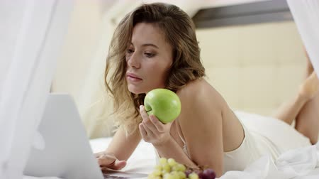 Woman reading news on her laptop and holding apple