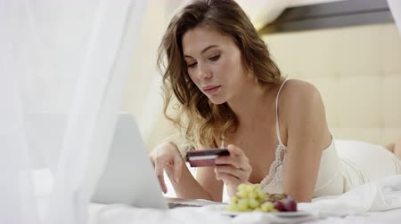 Sexy woman lies on bed and using her laptop and credit card