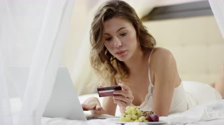 Pretty woman dressed in sleepwear lies on bed and using her laptop and credit card