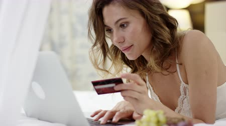 Tender woman dressed in sleepwear lies on bed and using her laptop and credit card for online shopping
