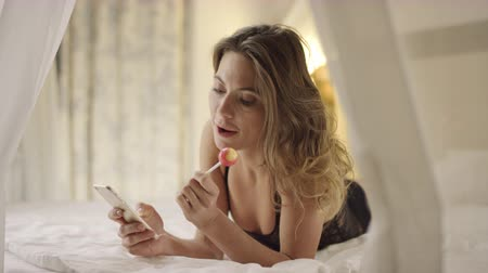 emmek : Sexy woman using smartphone and licking hard candy on bed