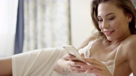 zmysłowy : Tender woman lying on bed and using smartphone