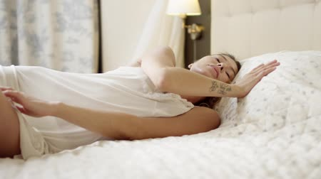 linen : Young woman posing on bed in sexy white sleepwear shirt