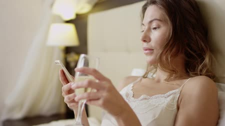 szampan : Woman lying in bed with a glass of champagne and a smartphone