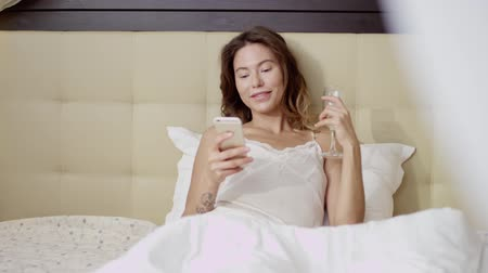 hazugság : Attractive woman lying on bed with a glass of champagne and a smartphone