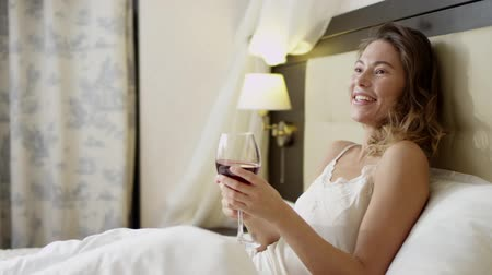 female linen : Young woman drinks red wine on bed Stock Footage