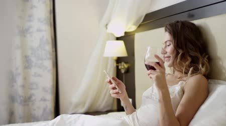 благодать : Woman texting over smartphone while drinking white wine on bed
