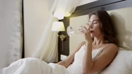 благодать : Young woman talking over smartphone while lying in bed with a glass of red wine