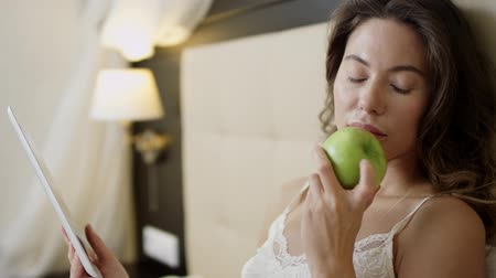 bed linen : Woman with tablet pc and an apple in bed