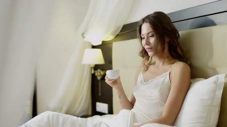 linen : Young woman with laptop drinking coffee on bed