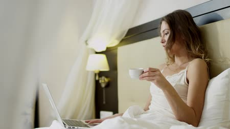 hazugság : Woman having a video chat on her laptop on bed while drinking coffee