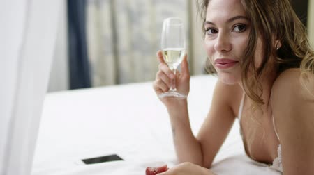 winogrona : Woman drinks champagne and eats fruits on bed