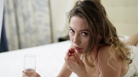linen : Charming woman drinks white wine and eats grape on bed