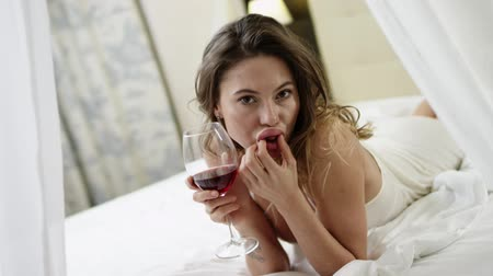 zmysłowy : Attractive woman drinks red wine and eats grape on bed