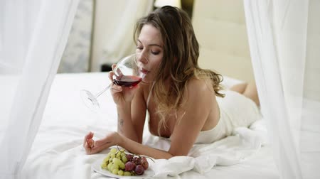 magro : Pretty woman drinks wine and eats grape on bed