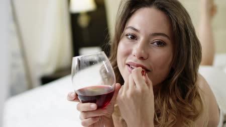 hazugság : Tender woman drinks red wine and eats grapes on bed