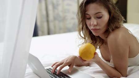 благодать : Beautiful woman with a laptop and orange on bed Стоковые видеозаписи