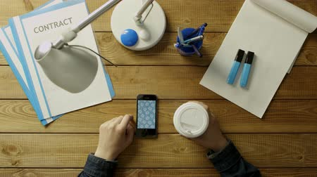 touchpad : A man is sitting at the office desk in the phone and drink coffee. On the desk office supplies in blue and white tones.