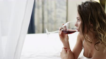 yalan : Attractive woman drinks wine lying in bed