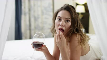 kırmızı şarap : Woman drinks red wine and eats grape while lying in bed