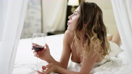 благодать : Young woman drinks red wine and eats grape while lying in bed and looks into the camera with passion Стоковые видеозаписи