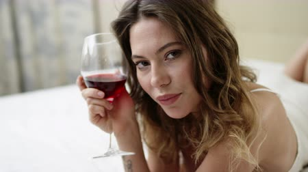 winogrona : Young woman dressed in sexy white sleepwear drinks wine and eats grape while lying in bed