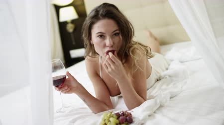 zmysłowy : Gorgeous woman drinks red wine and eats grape while lying on bed