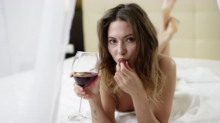 нежный : Young woman dressed in sexy white sleepwear drinks red wine and eats grape while lying in bed