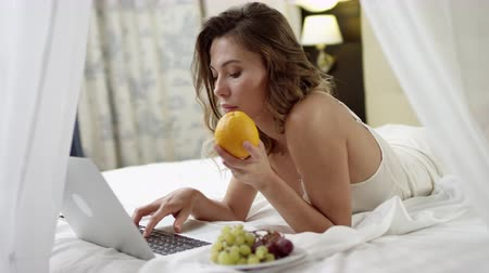 yalan : Young woman reading news on her laptop and holding and orange with grapes on plate near her