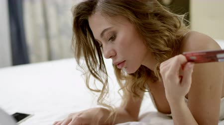 искушение : Woman buying something online on her bed by using her laptop and credit card