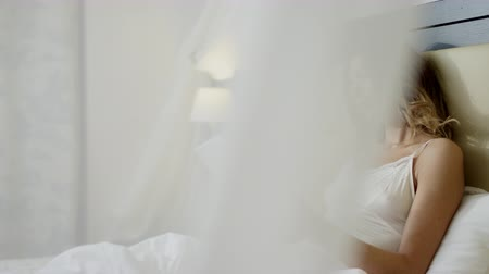 mentiras : Young beautiful woman lies in bed with tablet pc Vídeos