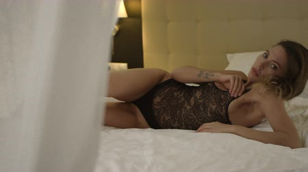 linen : Beautiful woman lies in bed and shows sexy poses in black underwear Stock Footage