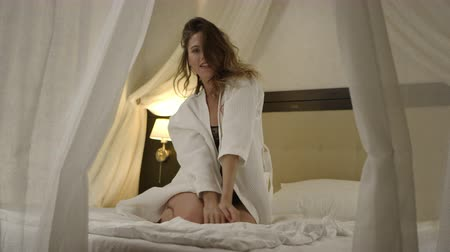 hazugság : Woman posing on bed in black catsuit and white bathrobe and stroking herself Stock mozgókép