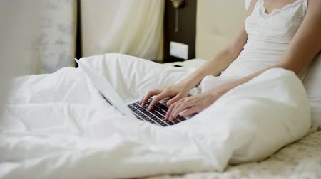 искушение : Attractive woman typing on laptop keyboard on bed Стоковые видеозаписи