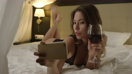 linen : Beautiful woman drinks red wine and taking a selfie on bed