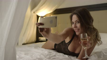 hazugság : Woman in lingerie drinks wine on bed and taking a selfie on smartphone
