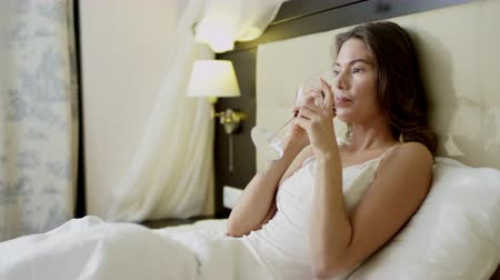 благодать : Pretty woman lies in bed and drinks red wine out of glass while speaking over smartphone