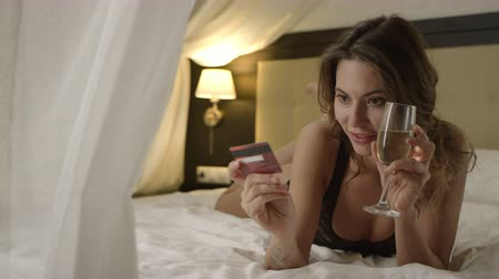 благодать : Woman in underwear posing with credit card on bed with a glass of champagne