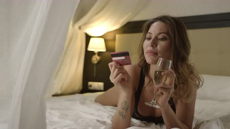 hazugság : Woman with a glass of white wine posing with credit card on bed