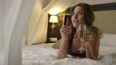 hazugság : Charming woman with a glass of champagne posing with credit card