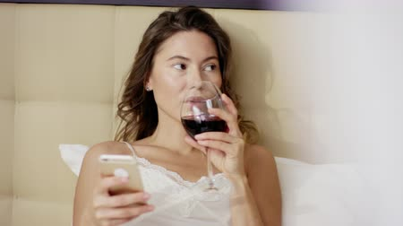 laying : Pretty woman lies on bed with smartphone and drinks red wine out of glass
