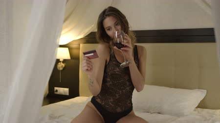 благодать : Attractive woman with a glass of wine posing with credit card on bed Стоковые видеозаписи