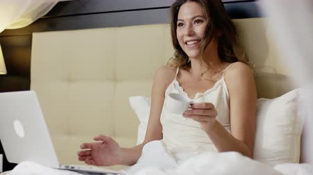 благодать : Sexy woman lies in bed, drinks coffee and having a video conversation over her laptop