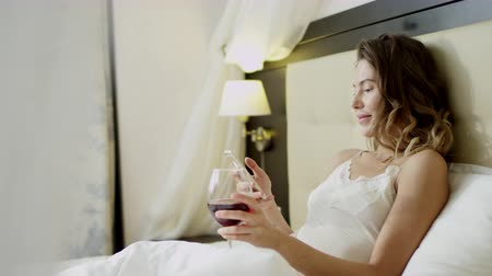 искушение : Woman lies in bed with a glass of red wine and reading news on her smartphone