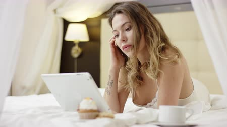 искушение : Attractive woman texting over a tablet pc while lying on bed near cup of coffee and cupcake