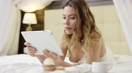 кровать : Attractive woman watching video on her tablet pc while lying near with cup of coffee and cupcake