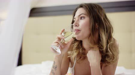 tek başına : Woman drinks champagne with cupcake on bed