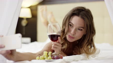 yalan : Attractive woman drinks red wine and takes selfie on her smartphone on bed Stok Video